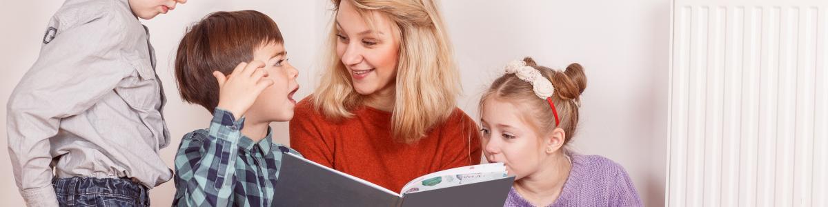 En kvinde læser op for nogle børn. Svært at se, om det er hendes egne, eller om hun har lånt dem