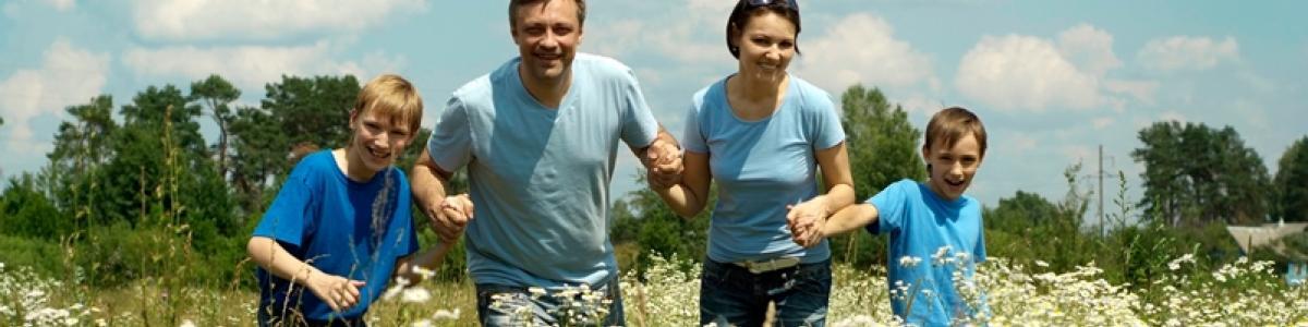 Glad familie: far, mor og to børn hånd i hånd gennem et yndefuldt marklandskab