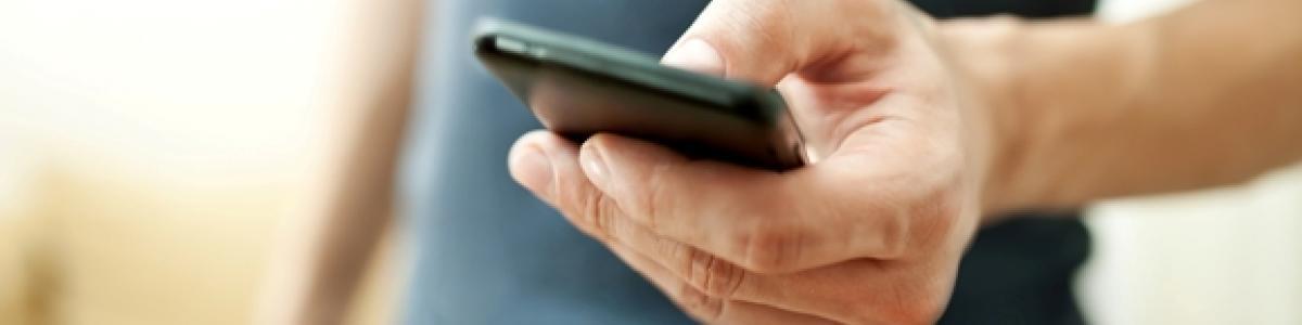Mand i sin bedste alder med håndholdt og bærbar mobiltelefon i hånden