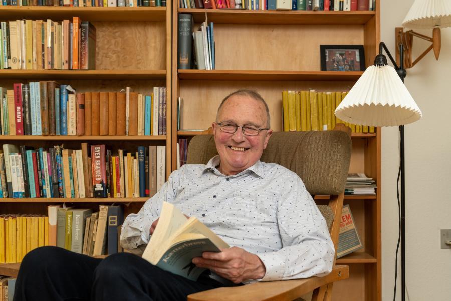 Hans Vesterager i lænestol med en bog i skødet. I baggrunden en bogreol.