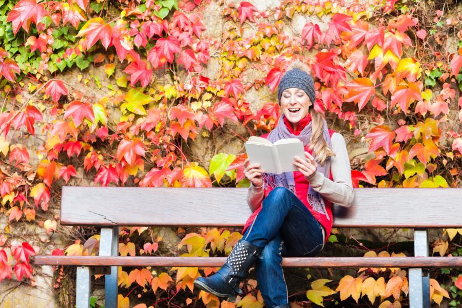 Billedet forestiller en kvinde, der sidder på en bænk med en bog. Væggen bag hende er dækket af smukke efterårsblade.