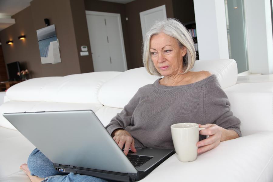 Ældre dame med en pc og en kop kaffe