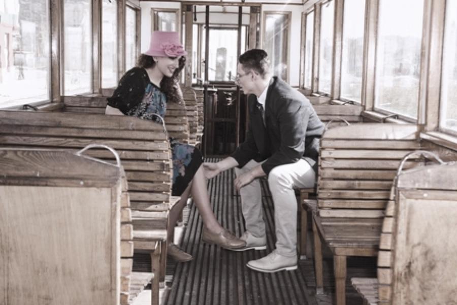 En mand og en kvinde i tøj fra 1940erne sidder i en sporvogn.