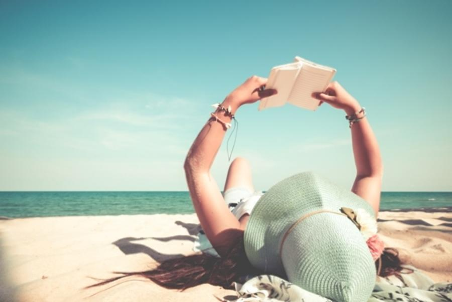 Billede af en kvinde der ligger på stranden og læser.