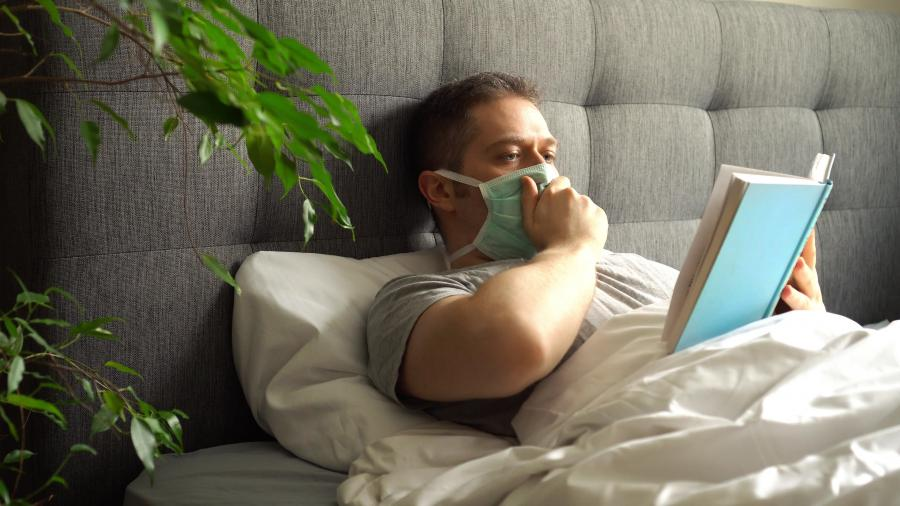Mand med mundbind læser bog