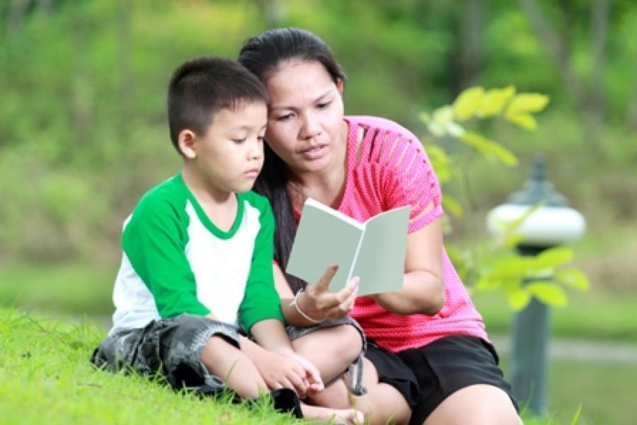 Billede af en kvinde der læser med sit barn.