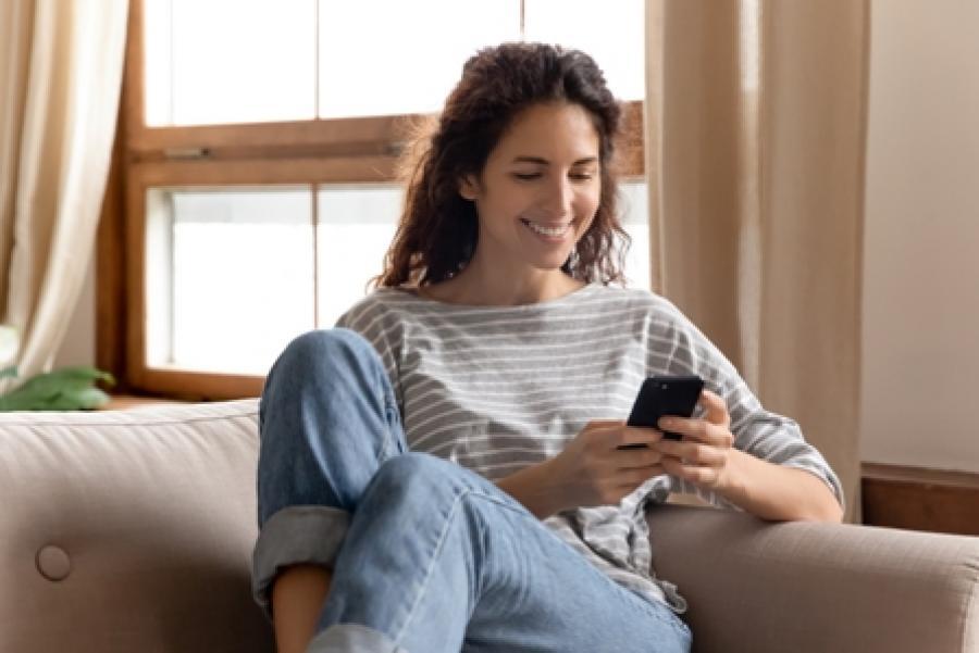 Kvinde sidder på sin sofa og ser smilende på sin telefon.