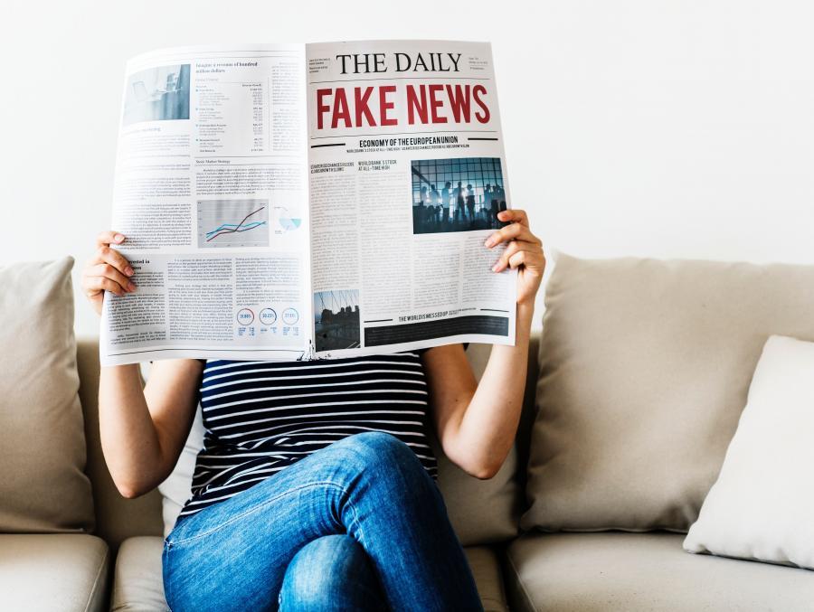 Kvinde sidder i en sofa med en avis foran ansigtet
