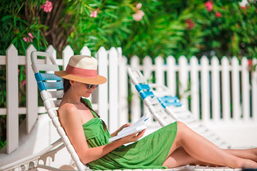 Billedet forestiller en kvinde på en solseng med en bog.