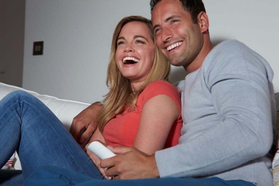 Foto af et par, der smiler og ser fjernsyn.