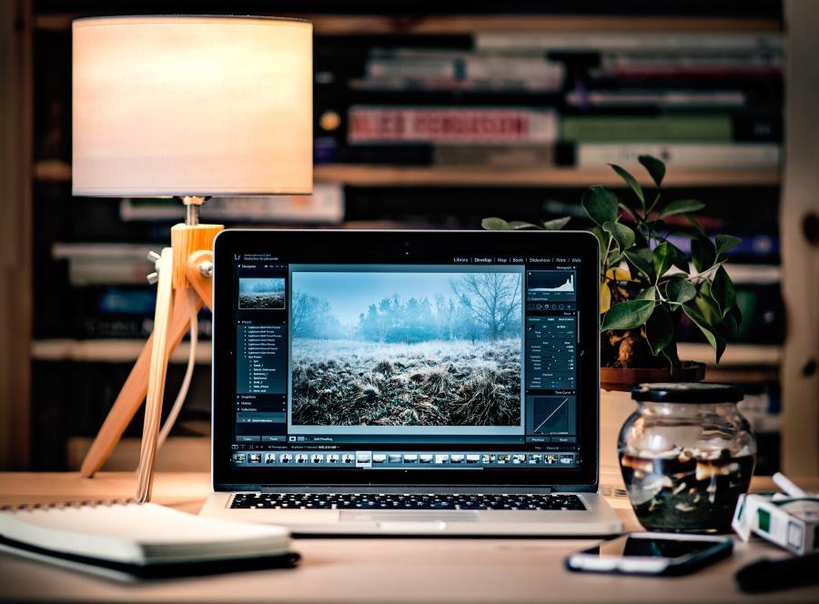 PC står på et skrivebord sammen med en tændt lampe. I baggrunden en bogreol