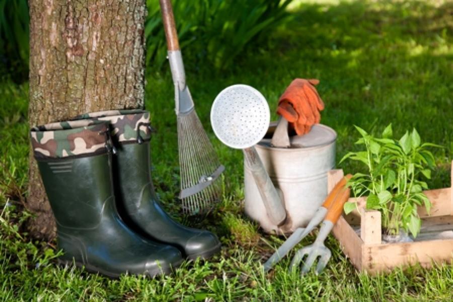Billedet forestiller forskellige haveredskaber som en vandkande, rive og gummistøvler.