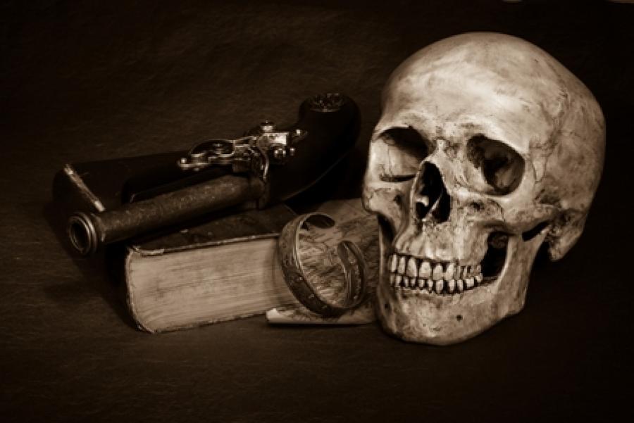 Et stemningsfyldt billede af en gammel bog, en pistol og et kranie.