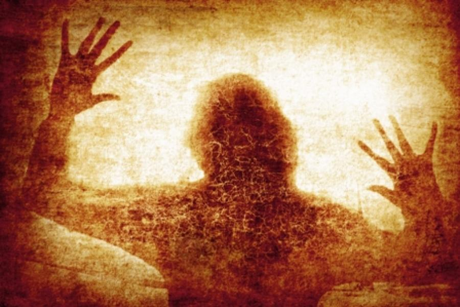 Billede af en uhyggelig skikkelse i et vindue.