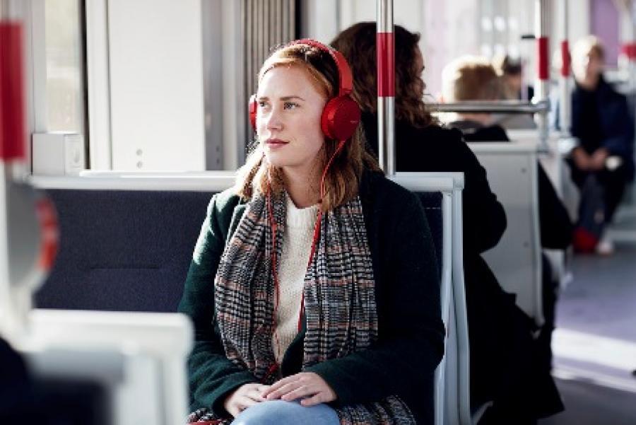 Billede af en ung kvinde der sidder i toget med høretelefoner på.