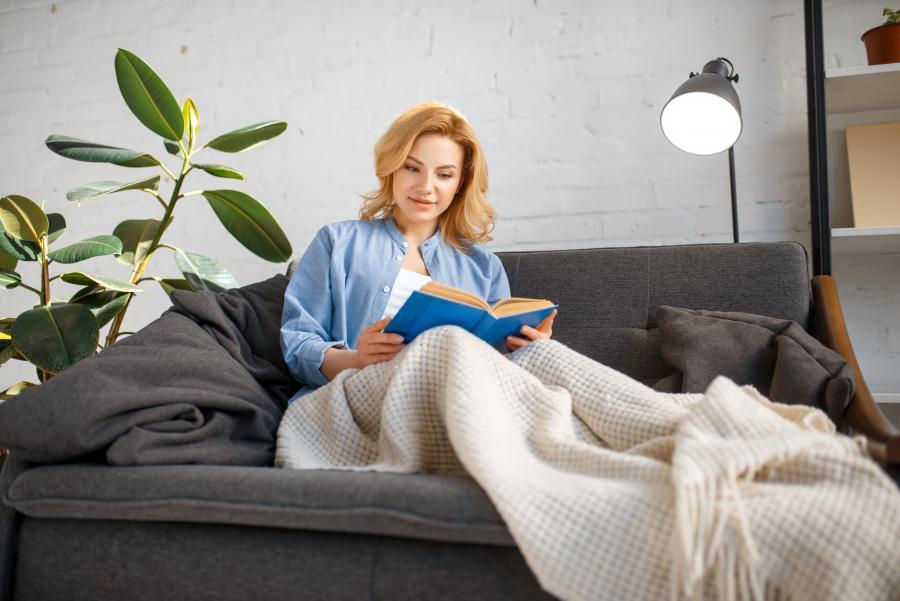 Billedet forestiller en kvinde, der sidder på en sofa med et tæppe over benene og læser.