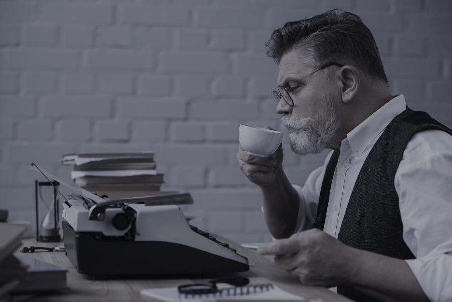 Billedet forestiller en mand med skæg der sidder ved en skrivemaskine.