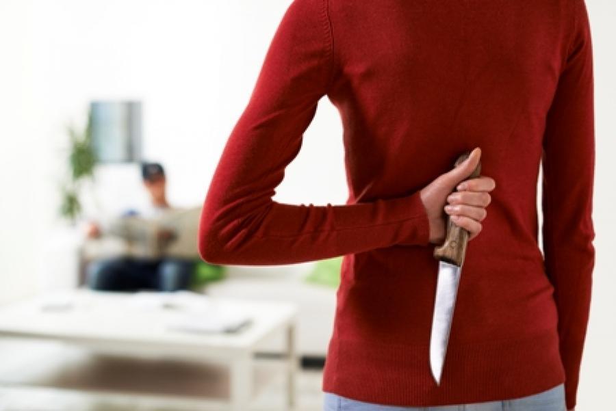 Billede af kvinde der gemmer en kniv bag ryggen.