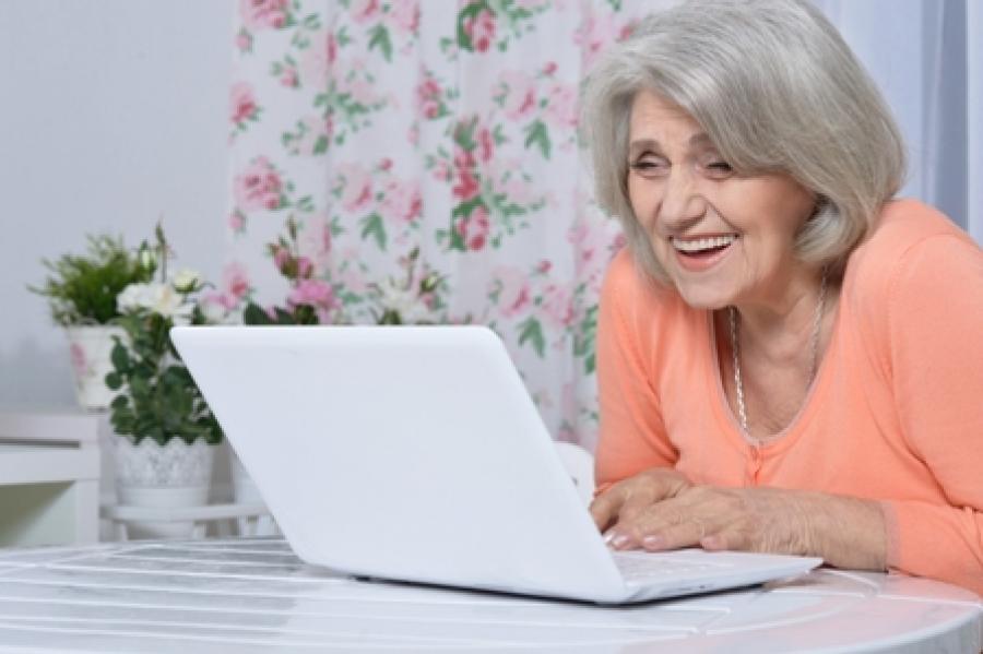 Kvinde smiler til computerskærmen.