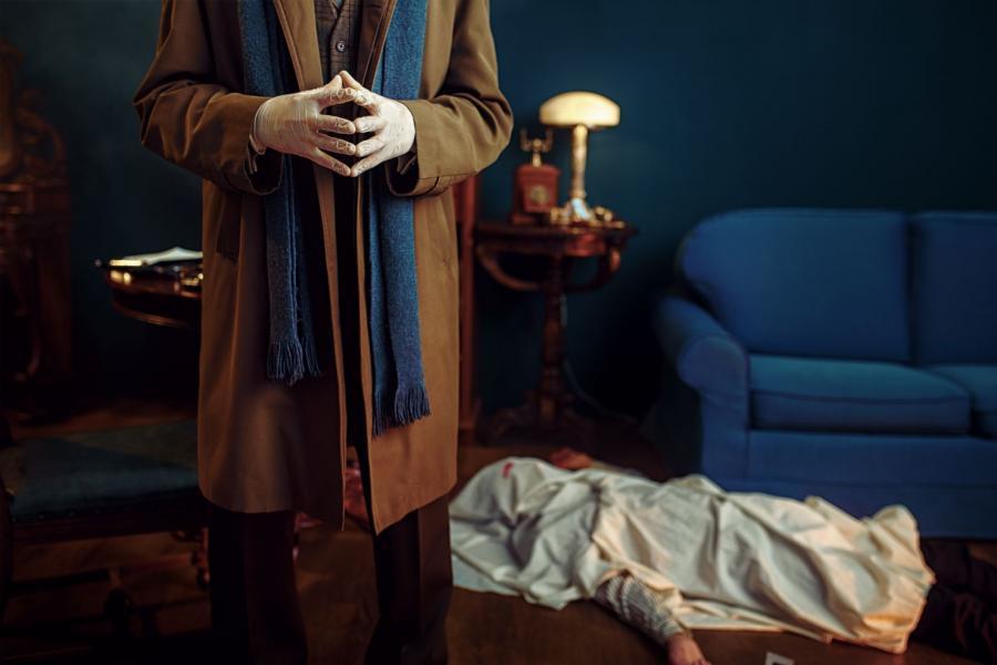 Billedet forestiller en mand i lang, brun frakke der står med hænderne samlet. Hænderne er klædt i latexhandsker, og bag manden kan man se et lig, der er overdækket med et hvidt lagen.