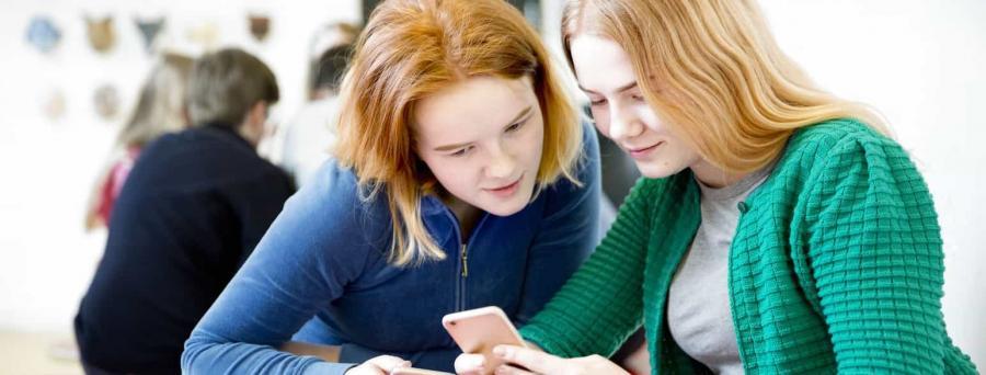 To unger kvinder kigger på en mobiltelefon