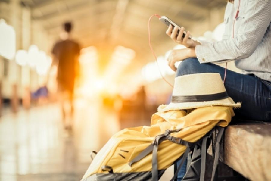 Billede af en person der sidder på en perron og lytter til sin telefon.