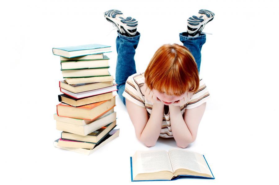 Ung pige læser med en stak bøger ved siden.