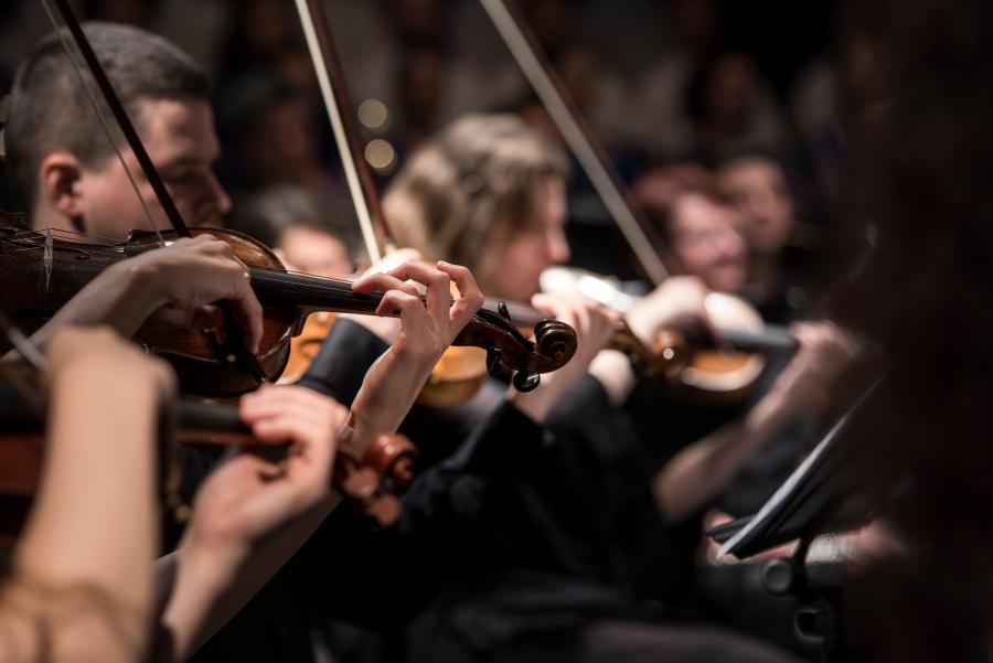 Nærbillede af pænt klædte violister ved klassisk koncert. Stemningen er lettere forførende