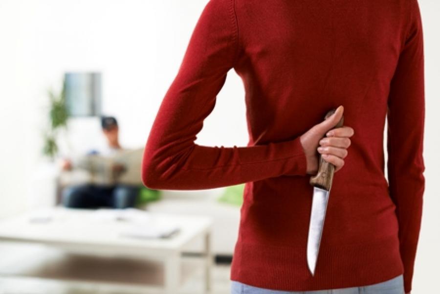 Kvinde holder en kniv skjult på ryggen.
