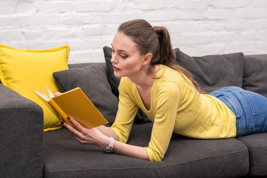 Billedet forestiller en kvinde i en gul trøje. Hun ligger på maven på en sofa med en bog i hænderne.
