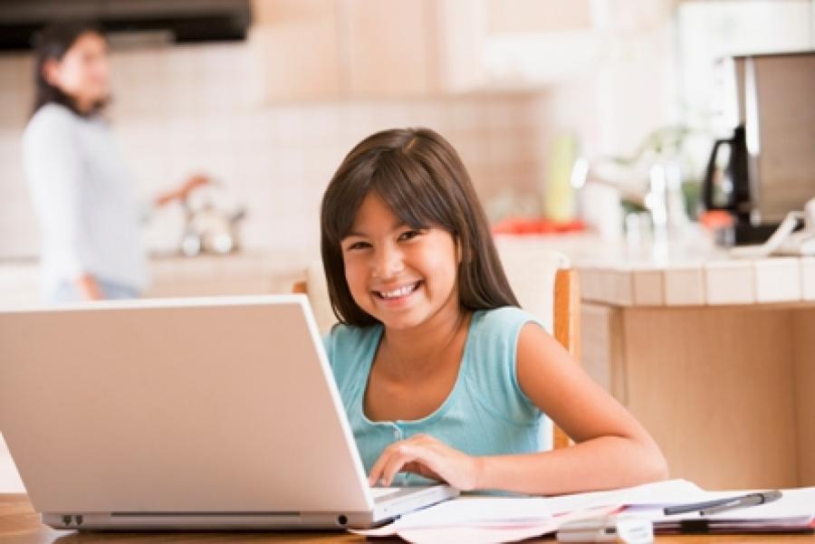 Billede af smilende pige foran computeren.