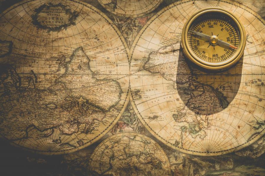 Gammelt landkort og kompas i brunlige nuancer