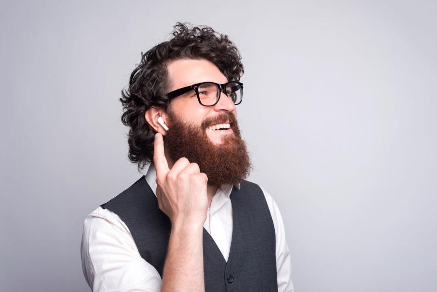 Billedet forestiller en ung mand med et stort, busket skæg. Han har earplugs i ørerne og lytter med et stort smil.