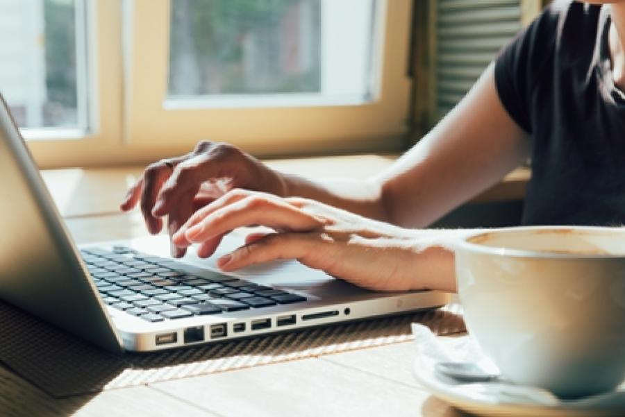 Nærbillede af hænder der hviler på en bærbars tastatur.