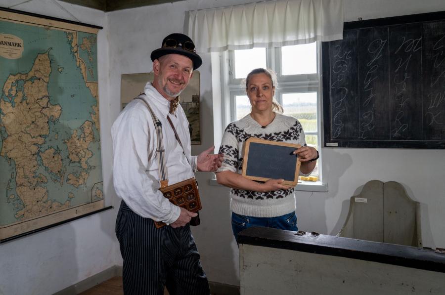 Billedet forestiller en mand og en kvinde, som står i en gammeldags skolestue. Kvinden har en gammeldags kridttavle i hænderne.