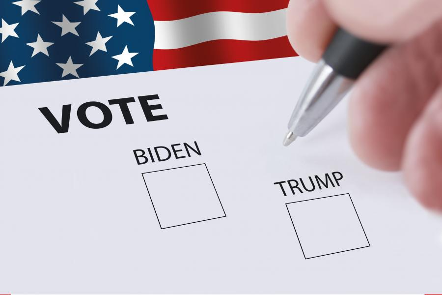 Amerikansk flag og en hånd med kuglepen, skal til at sætte kryds udfor biden eller Trump