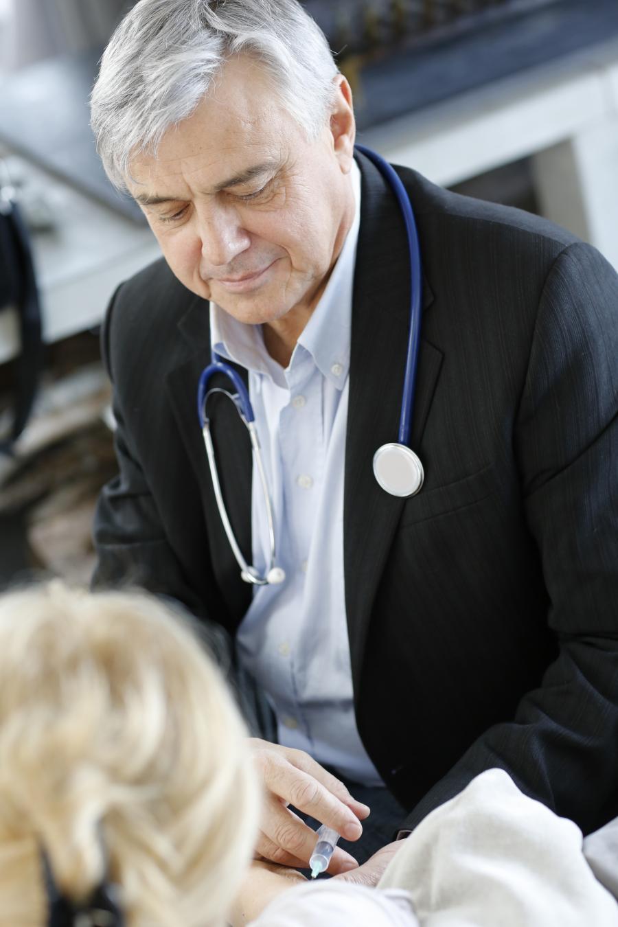 Ældre læge vaccinerer en kvinde